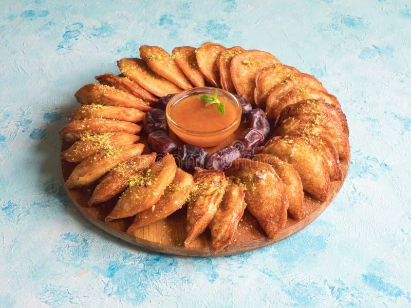 Dulces ?rabes Crepe ?rabe de Qatayef rellena con queso y nueces dulces en la tabla azul foto de archivo