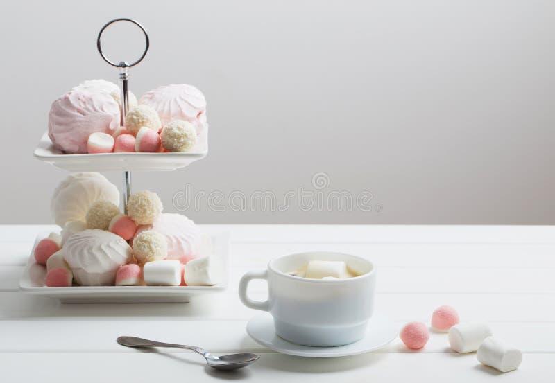 Dulces y taza de cacao con la melcocha foto de archivo