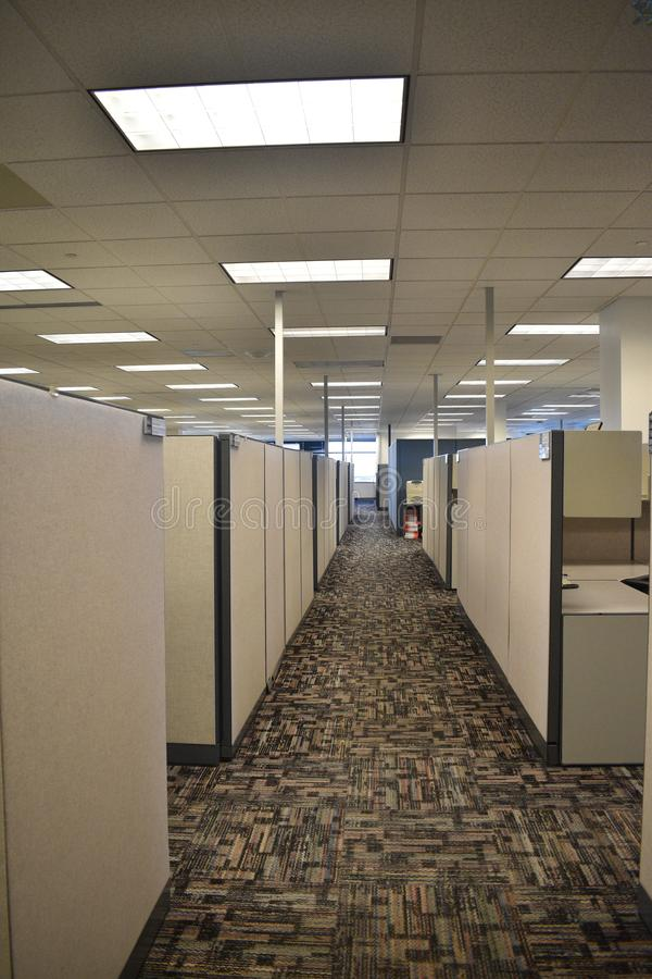 Dull empty office hallway in a cube farm with neutral colors. A dull hallway of an office building with many desks in a `cube farm`. Drop ceiling bad lighting royalty free stock photos