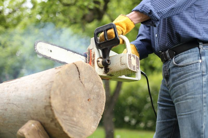 Dulled old chain of a Chainsaw. Man working with a Dulled old chain of a Chainsaw royalty free stock photos