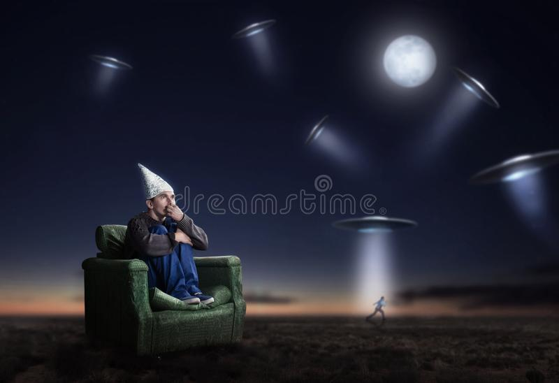 Dum man i tennfoliehjälm på natten, ufofobi arkivbilder