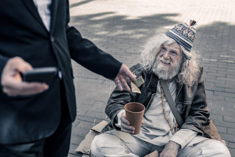 Dum oförsiktig affär som gör fotoet av handling av välgörenhet fotografering för bildbyråer