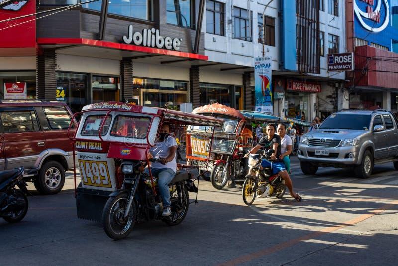 Dumaguete, οι Φιλιππίνες - 10 Μαρτίου 2019: Μοτοσικλέτα στην ασιατική οδό πόλεων Των Φηληππίνων τρίκυκλο και ποδήλατο Καφές Jolli στοκ εικόνες