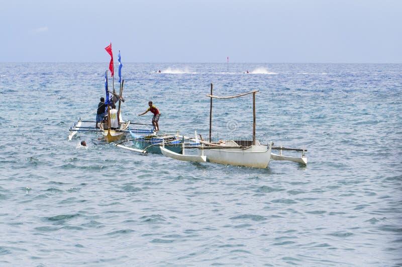 Dumaguete, Филиппины - 13-ое мая 2017: ландшафт моря с шлюпками и местными матросами Традиционная рыбацкая лодка в море стоковые изображения rf