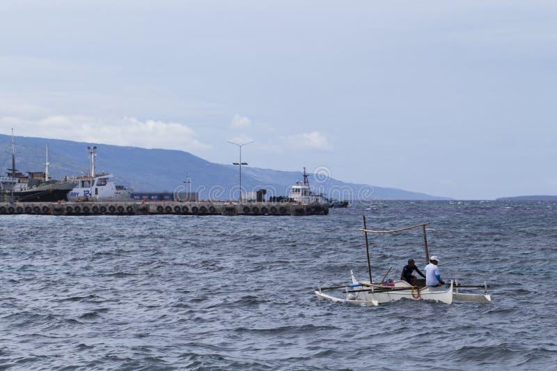 Dumaguete, Филиппины - 13-ое мая 2017: ландшафт моря с шлюпками и местными матросами стоковые фото