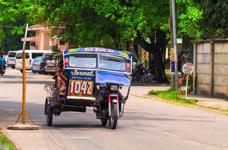 Dumaguete, Филиппины - 13-ое мая 2017: Национальный филиппинский трицикл перехода на улице города стоковая фотография