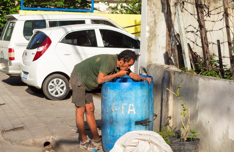Dumaguete, Filipinas - 6 de agosto de 2017: Alimento desabrigado da busca do homem no lixo pelo estacionamento do carro foto de stock royalty free
