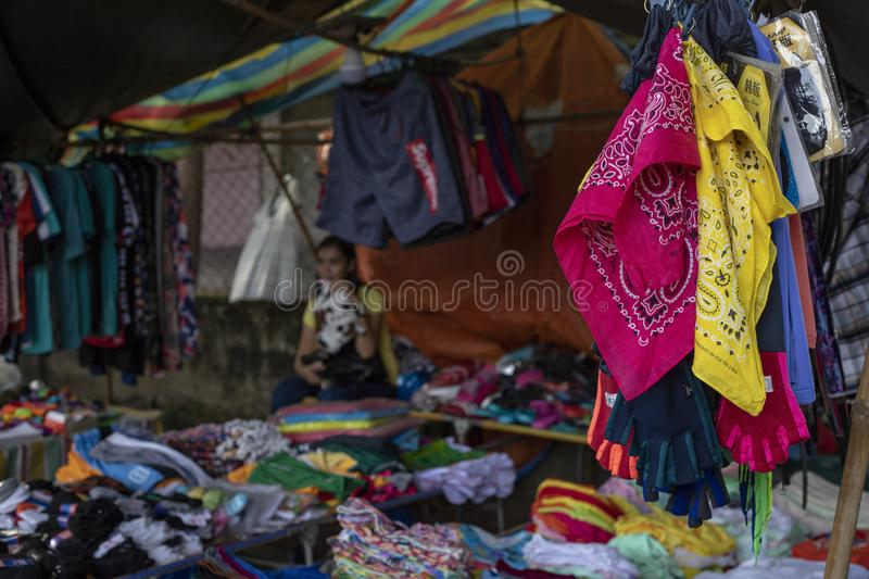 Dumaguete, the Philippines - 27 July 2018: Cheap colorful clothes on local market store. Second hand wear stall. stock photography