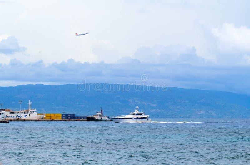 Dumaguete, Philippines - 13 mai 2017 : port de ville avec la silhouette d'île Bord de la mer urbain et transport maritime image stock