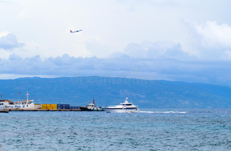 Dumaguete, Philippines - 13 May 2017: city port with island silhouette. Urban seaside and sea transport. Port shipping containers. Passenger flight over sea stock image