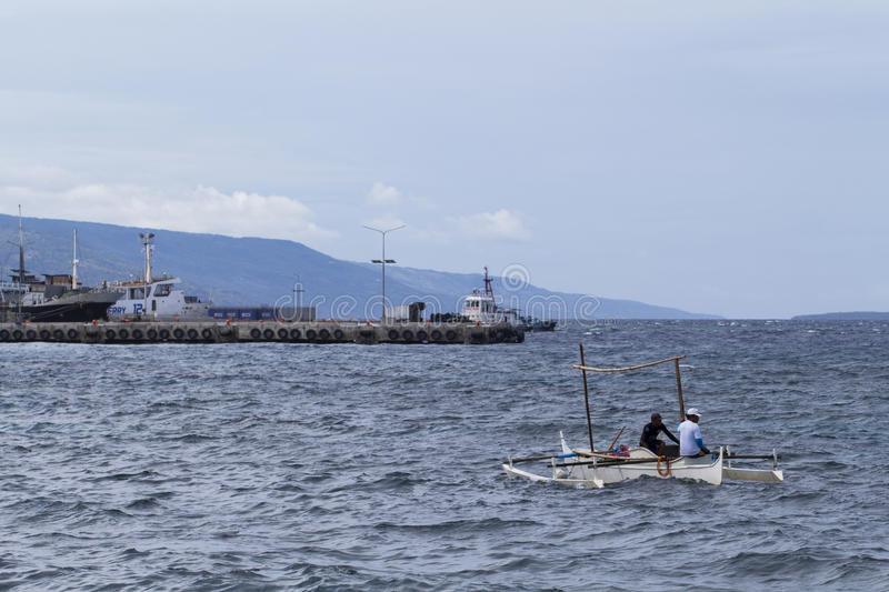 Dumaguete, Philippines - 13 May 2017: sea landscape with boats and local sailors. Urban seaside with sea port. Modern and traditional shipping. Fisherman boat stock photos