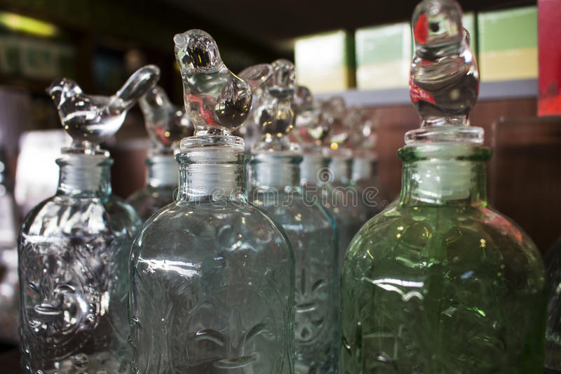 Dumaguete, Philippines - 26 November 2016: Glass ware home decor in shopping mall. Wine bottles with glass birds. Fancy glassware in shop. Shiny house decor stock photos