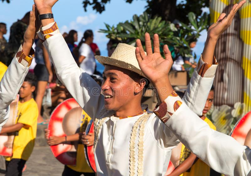 Dumaguete, Philippines - 16 September, 2017: Sandurot Festival dancer in grass hat. Carnival actor dancing in colorful costumes. Sunny day parade in royalty free stock photo