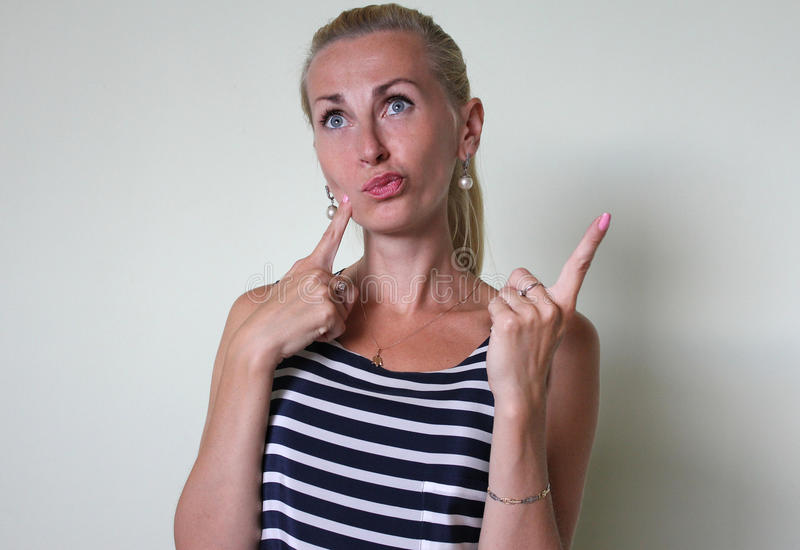 Dumb blond. White beautiful young girl, lady with long blond hair in a striped dress wondering, making a choice, considering, raising one finger to her cheek stock photos
