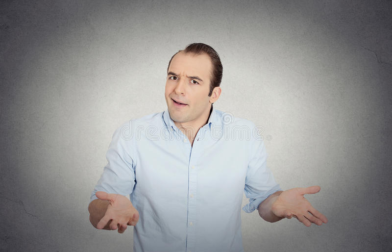Dumb clueless funny looking young man, arms out asking what's the problem royalty free stock photography