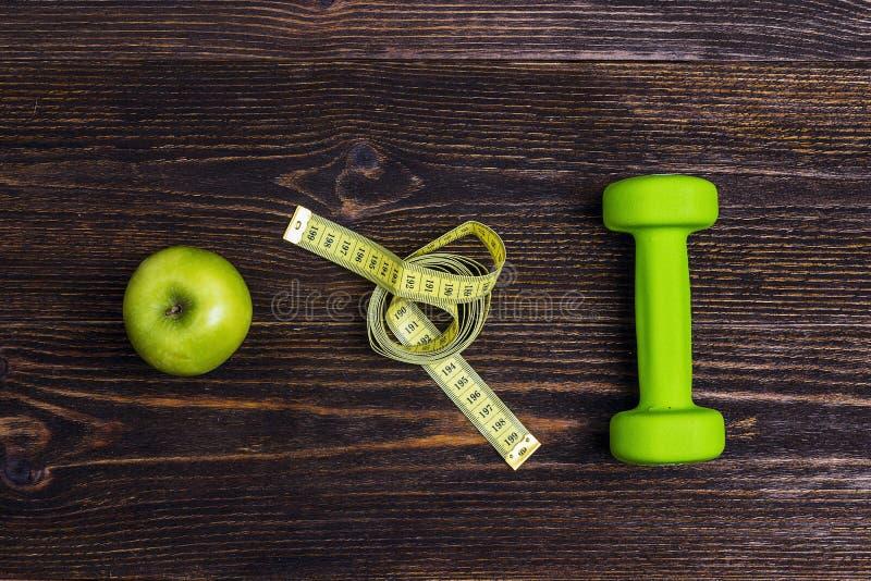 Dumbbel verde, maçã verde e fita de medição no backgrou de madeira foto de stock royalty free
