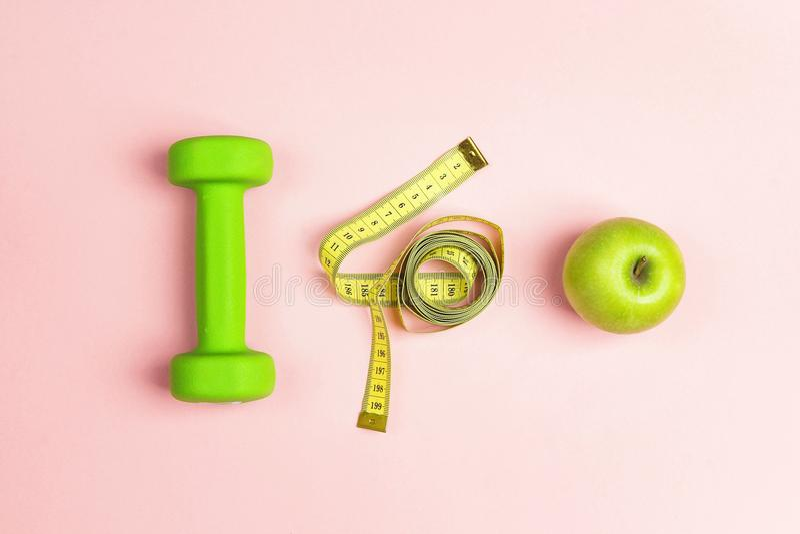 Dumbbel verde, maçã verde e fita de medição no fundo cor-de-rosa imagens de stock