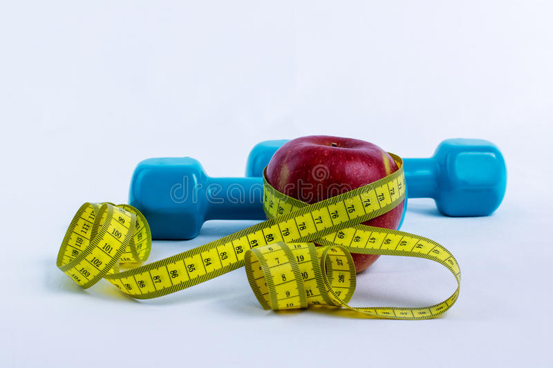 Dumbbell, apple and measuring tape. White background stock image