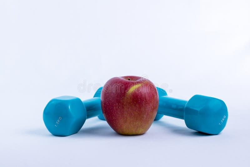 Dumbbell and apple white background sport. Dumbbell and apple white background stock image