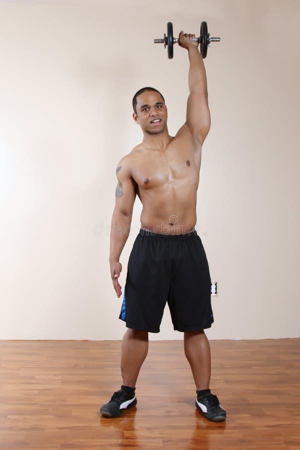 Dumbbell de levantamento do instrutor do peso com uma mão imagens de stock royalty free