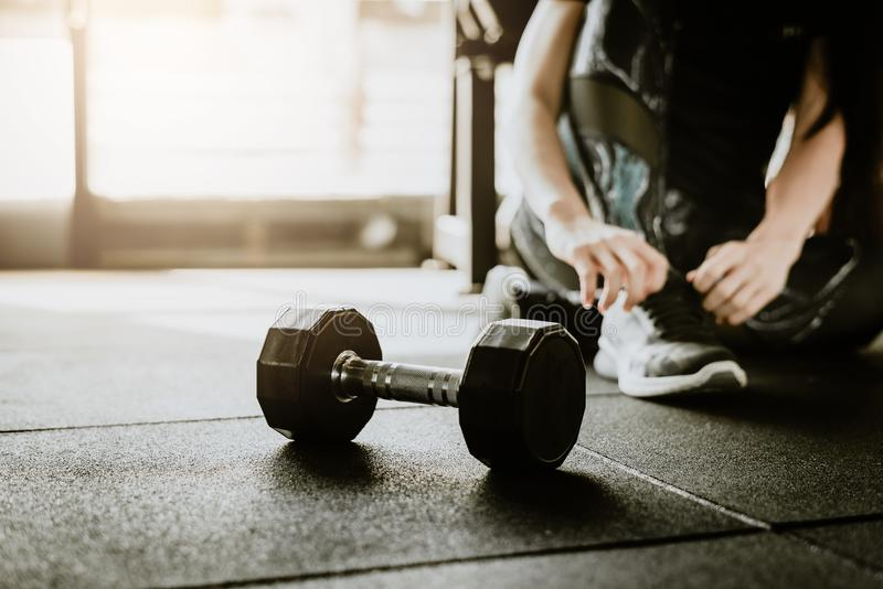 Dumbbell on the floor in gym with woman in background. Dumbbell on the floor in gym with woman tying her shoelaces before weight trainning in background. fitness stock photos