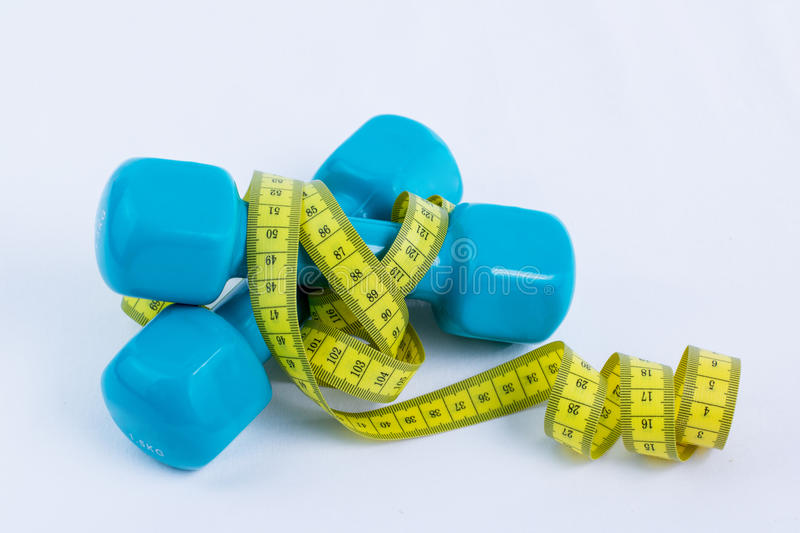 Dumbbell and measuring tape. Dumbbell apple and measuring tape royalty free stock photos