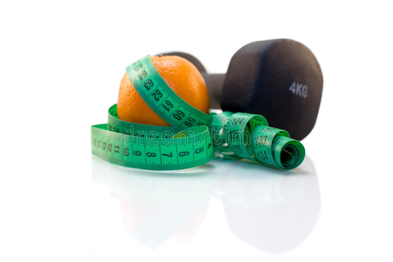 Dumbbell, orange and measuring tape on a white background. stock photos