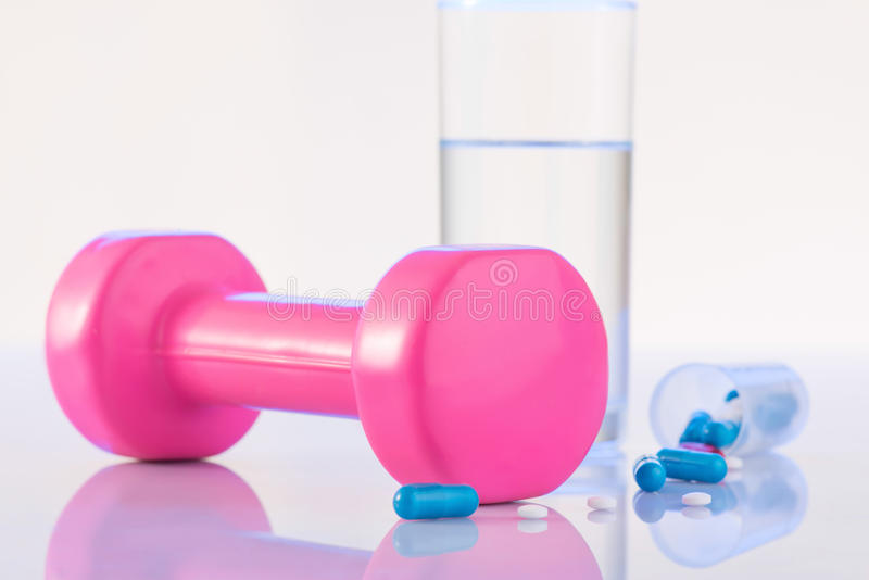 Dumbbell, pills and glass of water on the surface royalty free stock photo