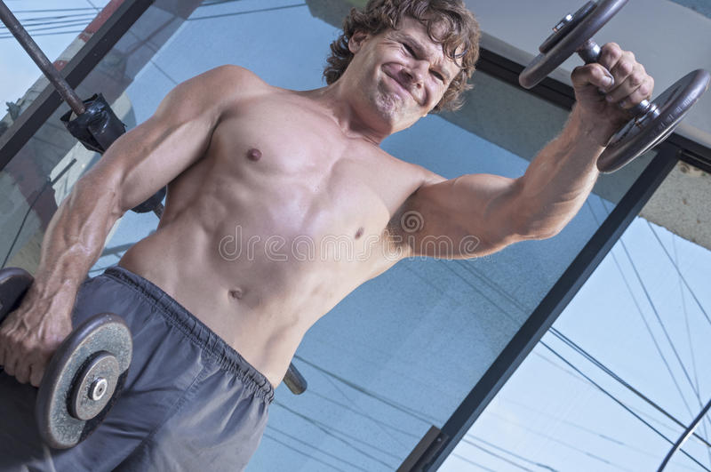 Dumbbell shoulder raises. Muscular shirtless Caucasian man with expression of exertion as he raises heavy dumbbell weight while performing front dumbbell raises stock photo