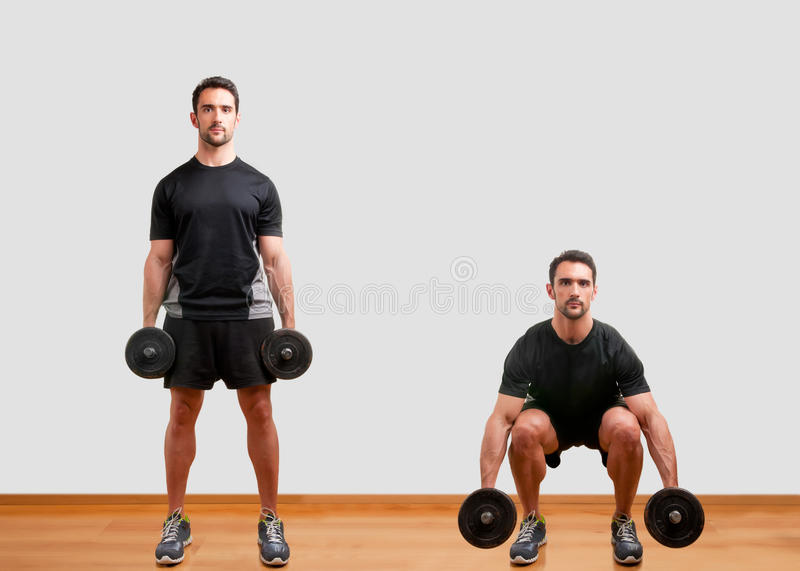 Dumbbell Squat. Personal Trainer doing dumbbell squat for training his legs royalty free stock photo