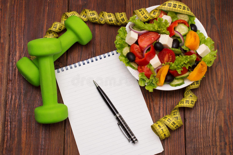 Dumbbell, vegetable salad and measuring tape on rustic wooden table. stock image