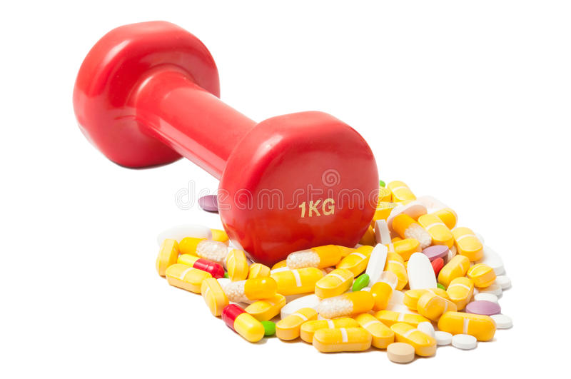 Dumbbell or weight and bunch of colored pills stock image