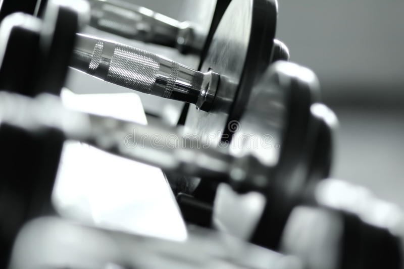 Dumbbell and Weights. A chrome dumbbell with extra weights stock images