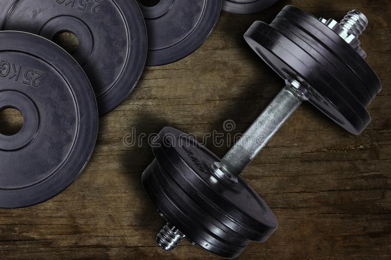 Dumbbell and weights on a wooden background stock image