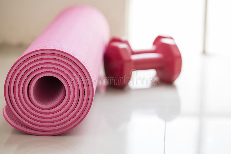 Dumbbell and yoga mat on table stock images