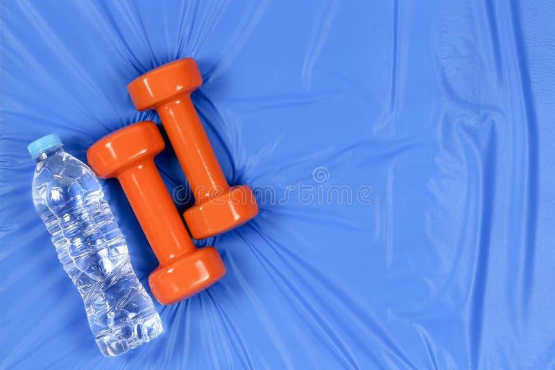Dumbbells on blue mat stock photography