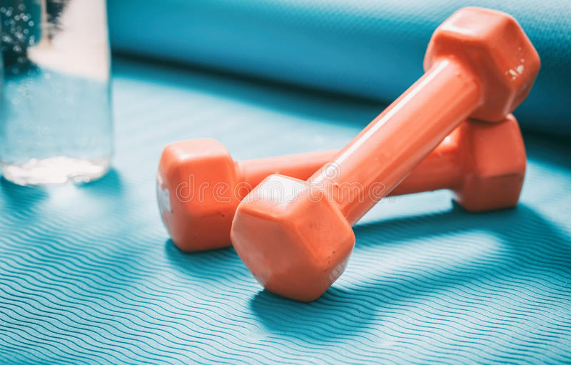 Dumbbells and a bottle of water on a yoga mat royalty free stock photo