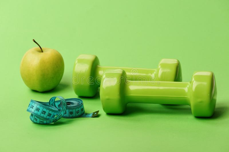 Dumbbells in bright green color, twisted measure tape and fruit stock images