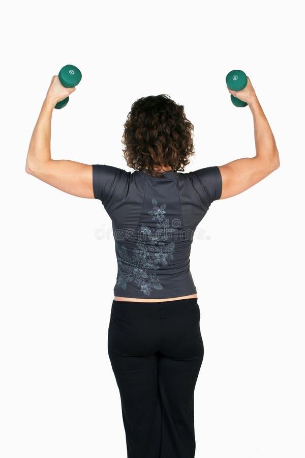 Dumbbells di sollevamento dell'istruttore femminile di forma fisica immagini stock libere da diritti