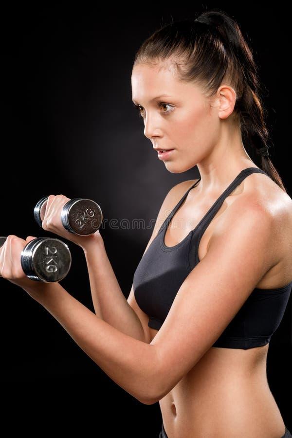 Dumbbells di sollevamento della giovane donna graziosa in abiti sportivi fotografie stock