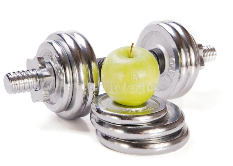 Dumbbells e mela verde su priorità bassa bianca immagine stock libera da diritti