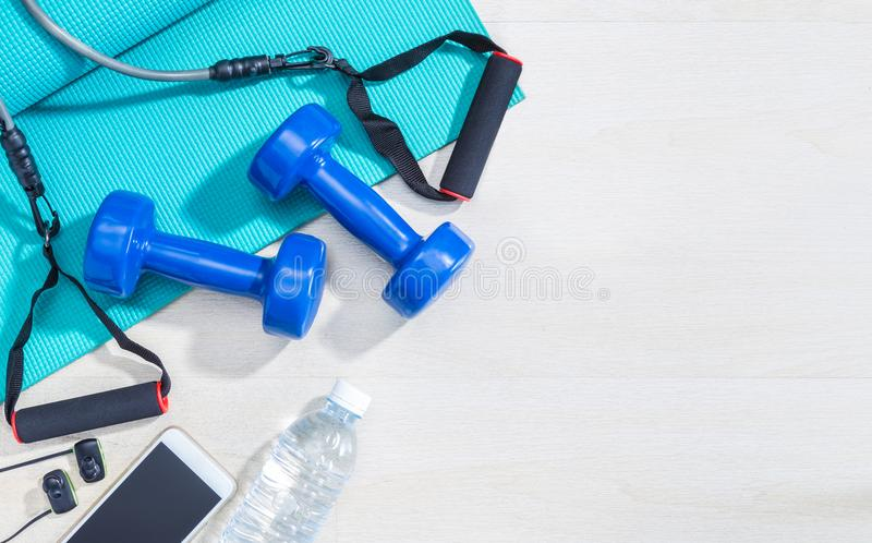 Dumbbells, excercise equipment, gym yoga mat, cellphone, earphones, and bottle of water on clean wood floor with strong bright mo. Rning light and hard shadow stock photography