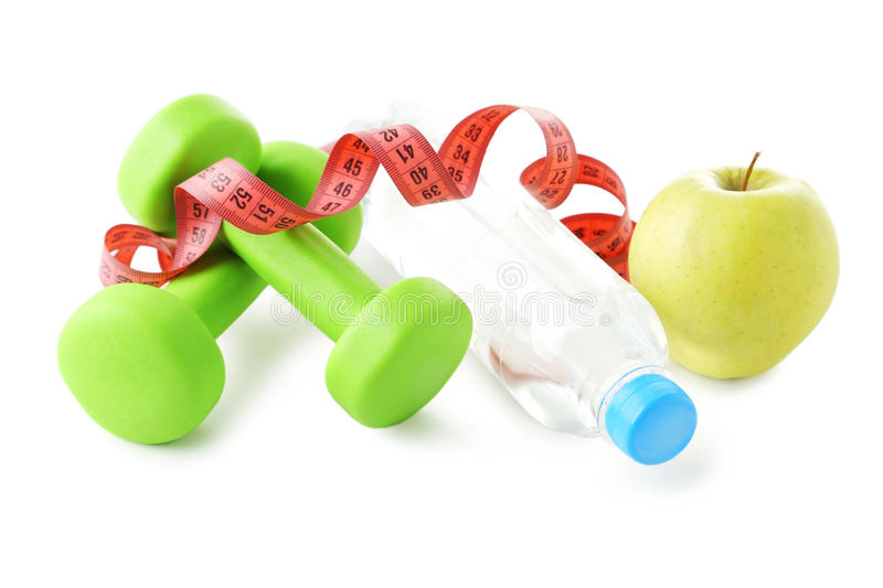 Dumbbells, green apple, bottle and tape measure royalty free stock photos