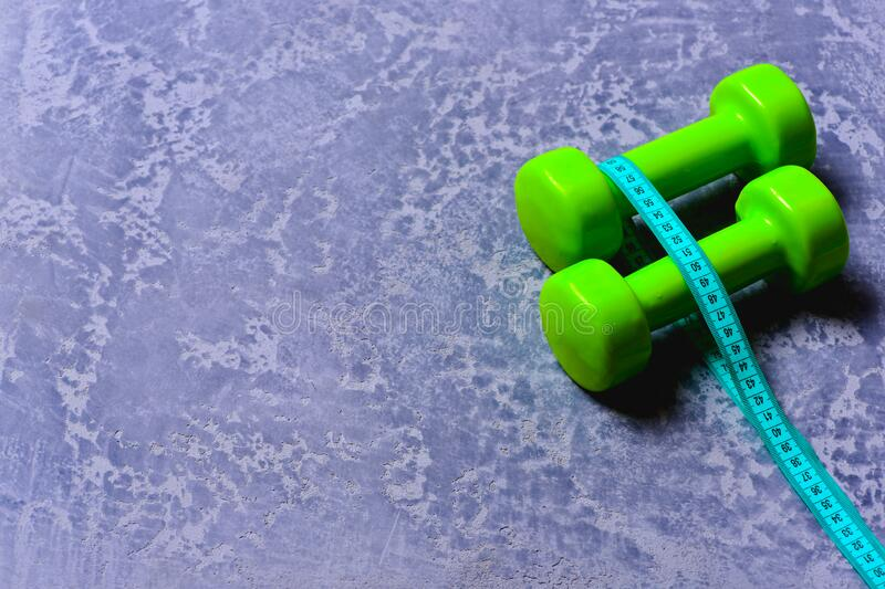 Dumbbells in green color and cyan measuring tape around them royalty free stock photos
