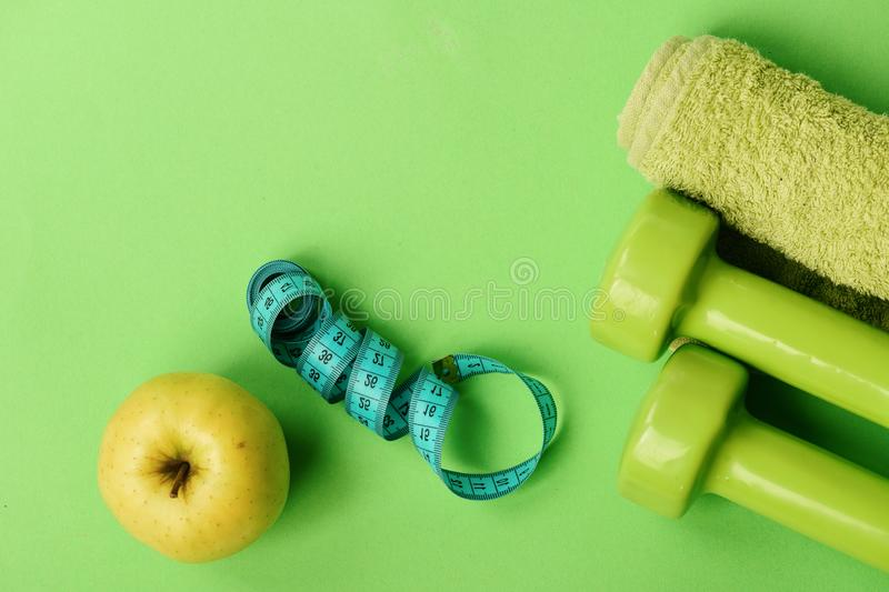 Dumbbells in green color, twisted measure tape, fruit and towel royalty free stock photo