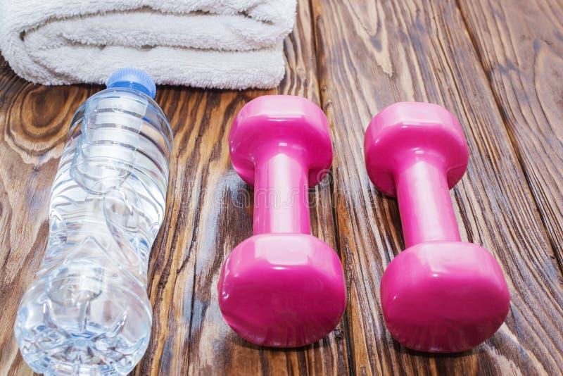 Dumbbells i butelka woda z ręcznikiem na drewnianym tle, pojęcie przygotowywa sprawność fizyczna sportów wyposażenia odgórny wido obrazy stock