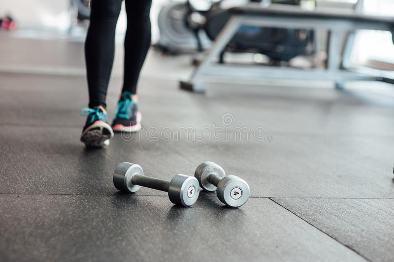 Dumbbells lie on the floor in the gym. In the background of athletic girls legs royalty free stock photography
