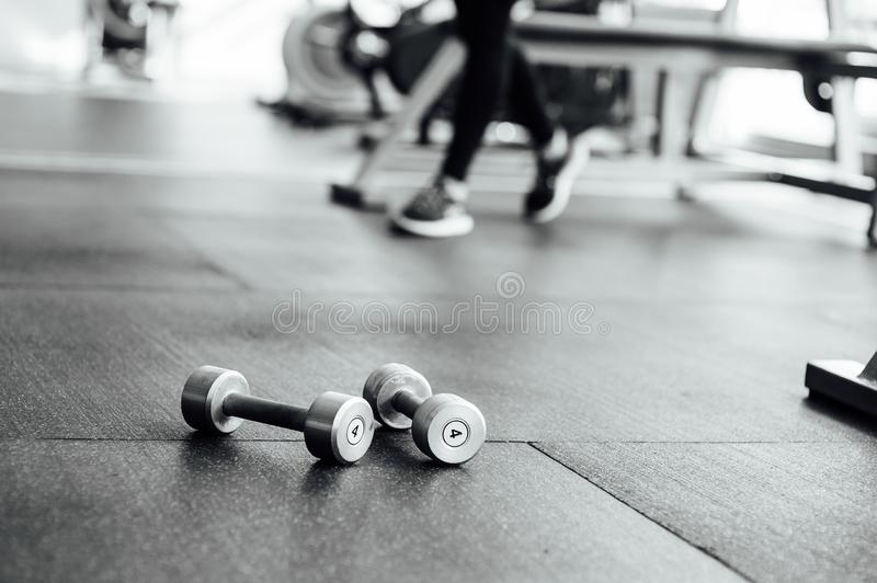 Dumbbells lie on the floor in the gym. In the background of athletic girls legs stock images