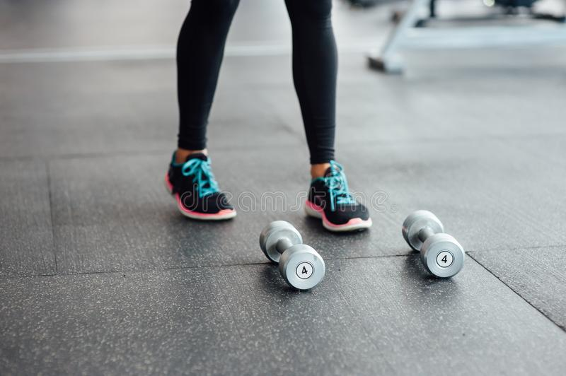 Dumbbells lie on the floor in the gym. In the background of athletic girls legs stock photography