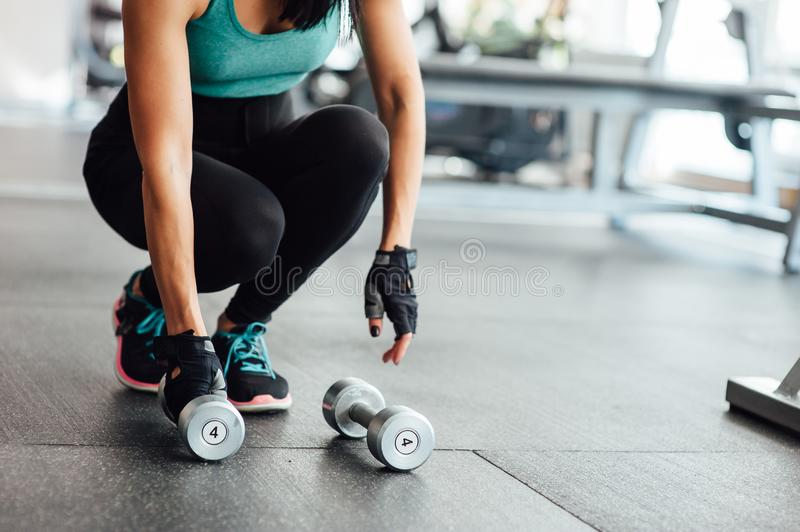 Dumbbells lie on the floor in the gym. In the background of athletic girls legs stock photo